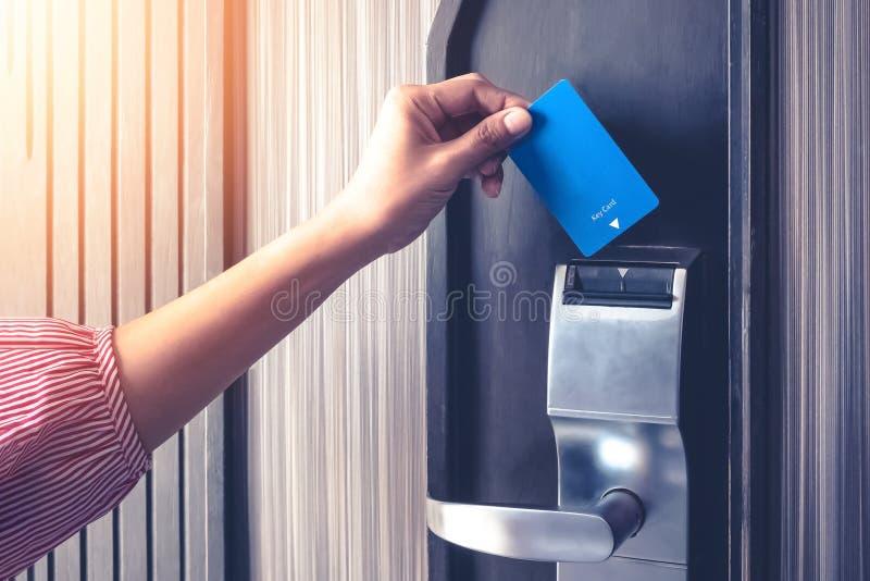 Mano que inserta la llave electrónica para desbloquear una autentificación de la seguridad de la puerta en la salvaguardia del ho imágenes de archivo libres de regalías