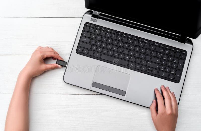 Mano que inserta memoria USB en el ordenador portátil en el fondo blanco Ciérrese para arriba de tapar de la mano de la mujer pen imagen de archivo