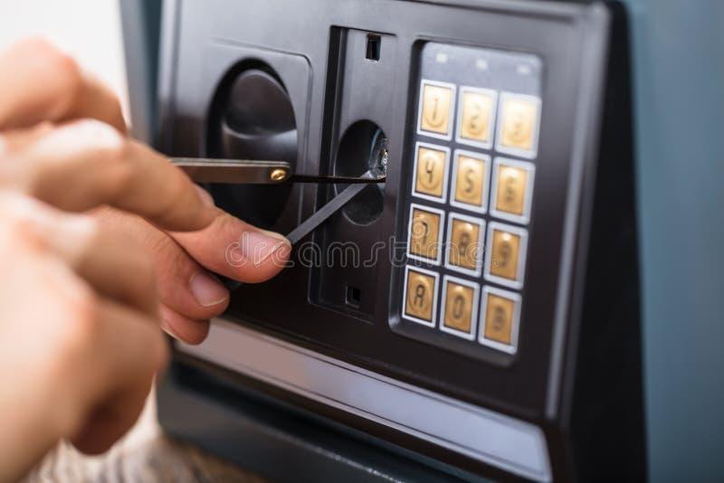 Mano que intenta romper la caja fuerte de la seguridad en el hogar fotos de archivo libres de regalías