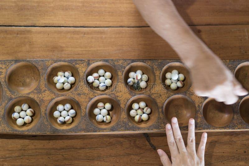 Mano que juega al juego de mármol Vetea el juego en tablero de madera fotos de archivo