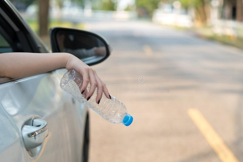Mano que lanza la botella plástica en el camino imagenes de archivo