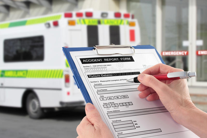 Mano que llena el formulario informe de accidente de Ambulan fotografía de archivo