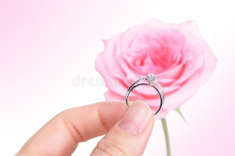 Mano que lleva a cabo el anillo de bodas romántico de diamante imagenes de archivo