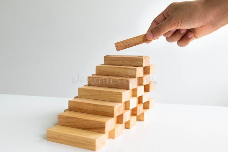 Mano que lleva a cabo el bloque de madera con el modelo de la arquitectura, el riesgo alternativo de planificación y la estrategi foto de archivo