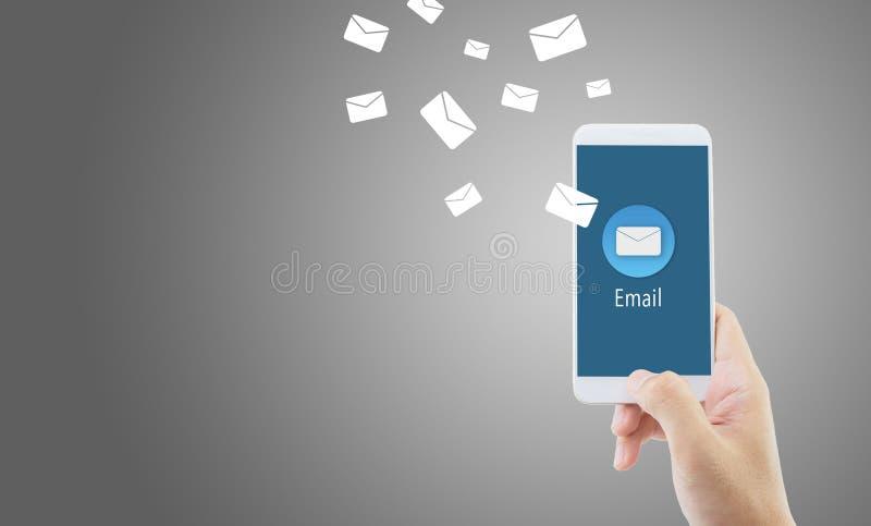 Mano que lleva a cabo el control del hombre y que envía el mensaje con el correo electrónico en un teléfono en fondo azul imagenes de archivo
