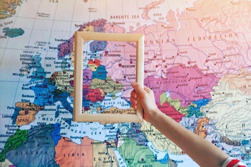 mano que lleva a cabo el marco de madera en el mapa de Europa foto de archivo
