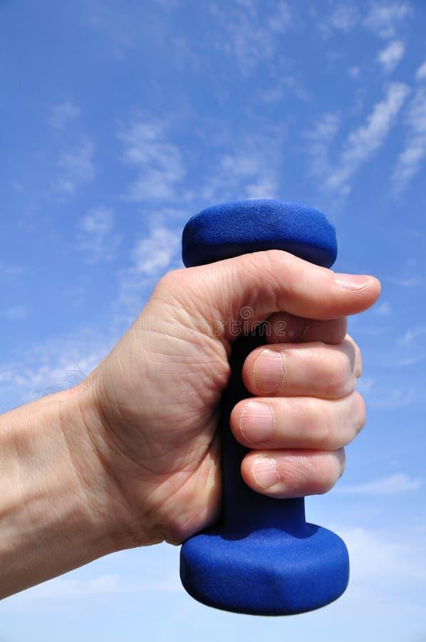 Mano que lleva a cabo el peso azul imagen de archivo libre de regalías