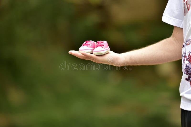 Mano que lleva a cabo el rosa del zapato del niño foto de archivo
