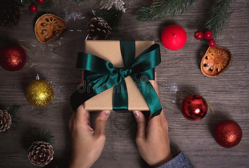 Mano que lleva a cabo el sistema del regalo del regalo de Navidad en fondo de madera de la tabla foto de archivo libre de regalías