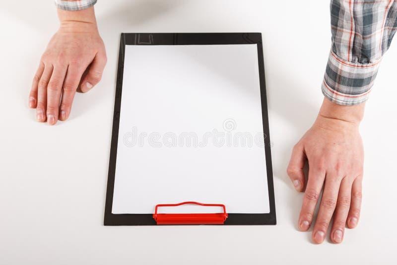 Mano que lleva a cabo el tablero de clip en blanco con la maqueta del diseño del Libro Blanco imágenes de archivo libres de regalías