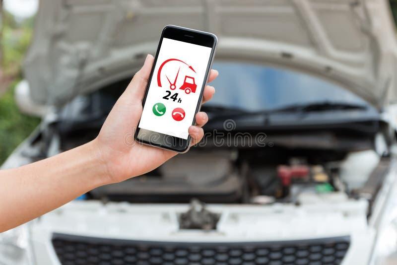 Mano que lleva a cabo la aplicación de servicios del coche de la emergencia de la llamada de teléfono imagen de archivo libre de regalías