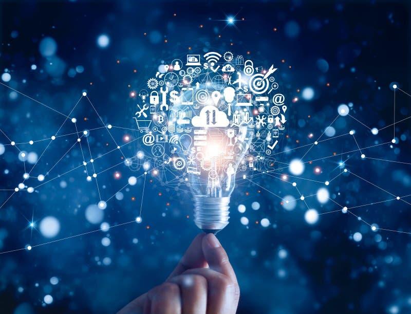 Mano que lleva a cabo la bombilla e iconos de comercialización digitales de la tecnología de la innovación del negocio en red