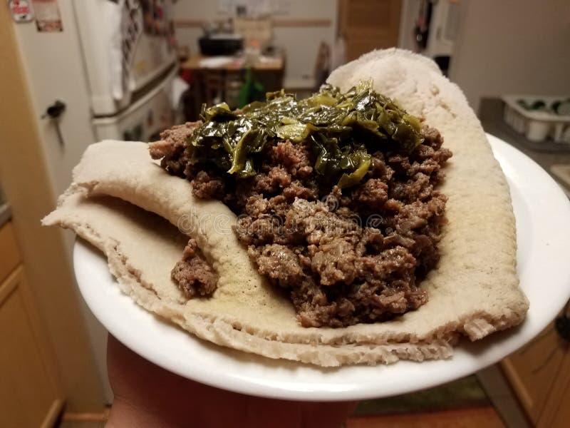 Mano que lleva a cabo la carne de vaca etíope y verdes de la comida en el pan en la placa fotografía de archivo