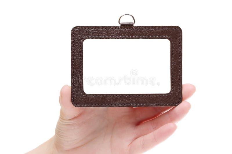 Mano que lleva a cabo la insignia en blanco de la identificación foto de archivo