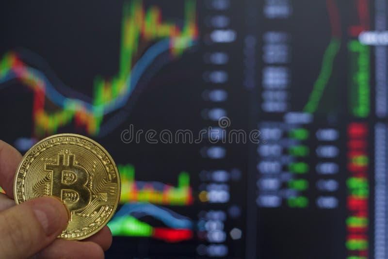 Mano que lleva a cabo la moneda de oro de Bitcoin y la carta defocused del mercado en el fondo imagenes de archivo
