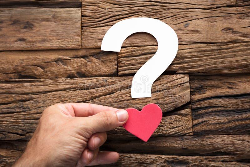 Mano que lleva a cabo la pregunta Mark With Heart On Wood fotos de archivo