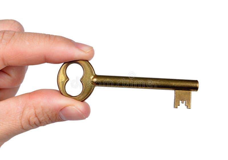 Mano que lleva a cabo llave de oro de la puerta imagen de archivo libre de regalías