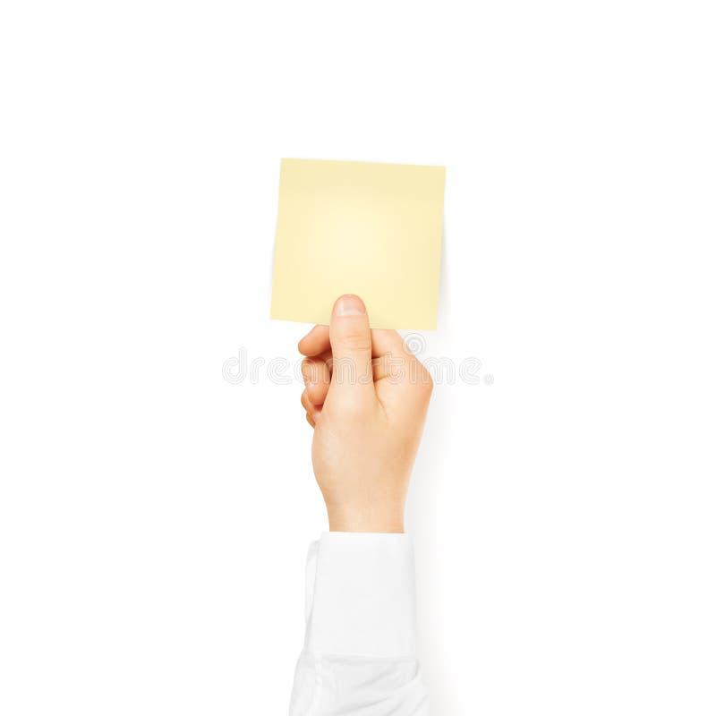 Mano que lleva a cabo mofa amarilla en blanco cuadrada de la etiqueta engomada para arriba aislada palillo imagen de archivo