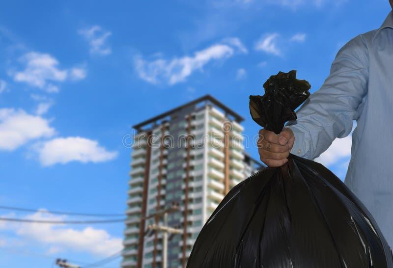 Mano que lleva a cabo negro del bolso de basura en el edificio y el cielo azul imagen de archivo