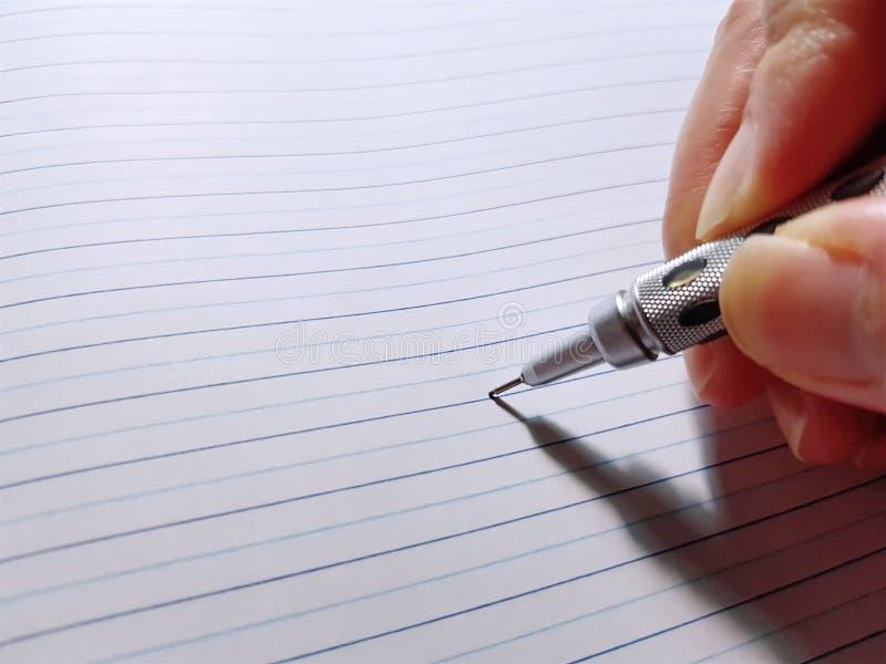 Mano que lleva a cabo notas mecánicas de la escritura del lápiz sobre el cuaderno foto de archivo