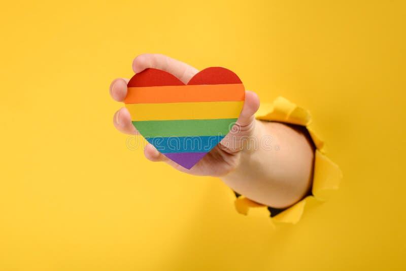 Mano que lleva a cabo un corazón del arco iris fotografía de archivo libre de regalías