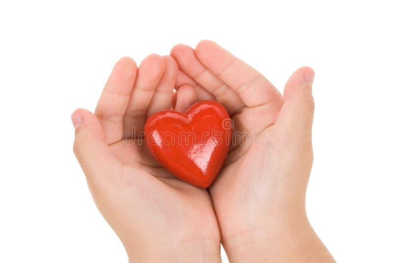 Mano que lleva a cabo un corazón rojo fotografía de archivo