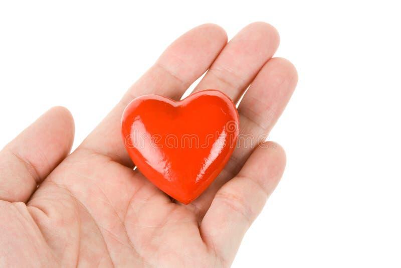 Mano que lleva a cabo un corazón rojo imagen de archivo