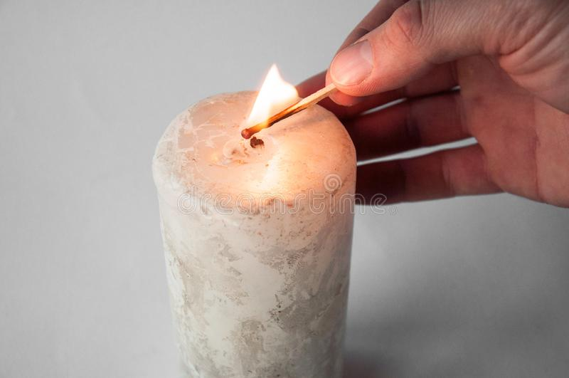 Mano que lleva a cabo un partido ardiente y luces a la vela fotografía de archivo libre de regalías