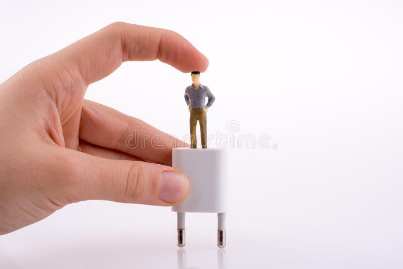 Mano que lleva a cabo una figura en un adaptador foto de archivo