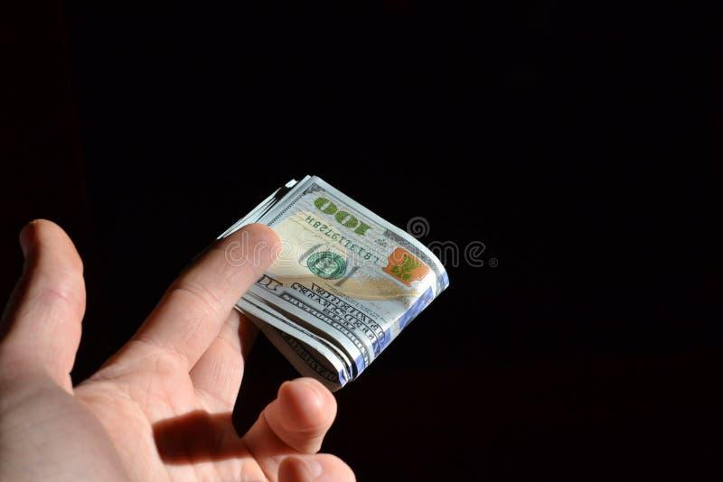 Mano que lleva a cabo varias notas del dólar foto de archivo libre de regalías