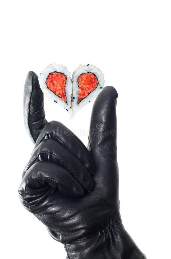 Mano que lleva el guante de cuero negro que lleva a cabo el corazón fotografía de archivo