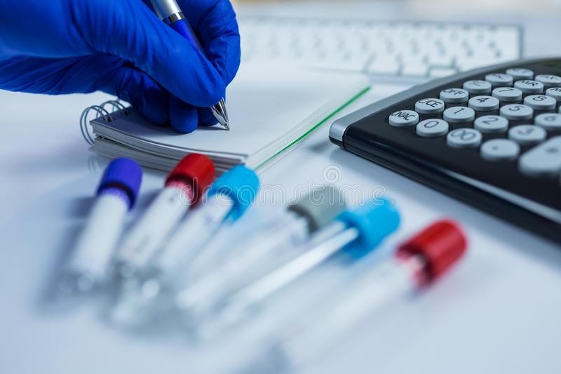 Mano que lleva los guantes azules que hacen notas al lado de las botellas para las muestras usadas en hospitales o medicina para  imagen de archivo libre de regalías