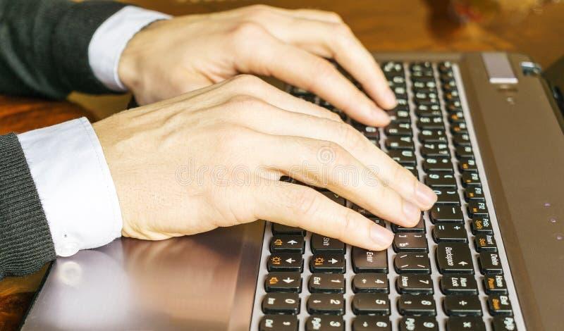 Mano que mecanografía en el primer del teclado del ordenador portátil Hombre de negocios usando un ordenador portátil foto de archivo