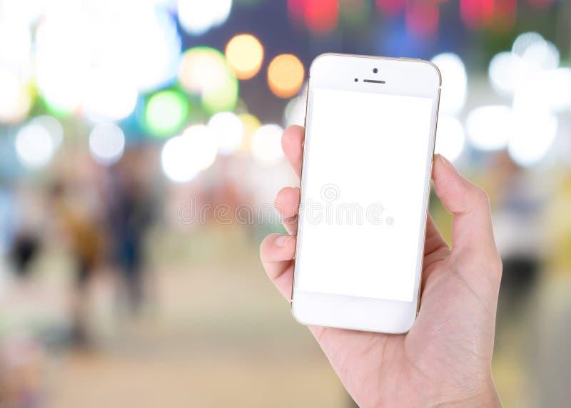 Mano que muestra a teléfono elegante la pantalla en blanco fotos de archivo