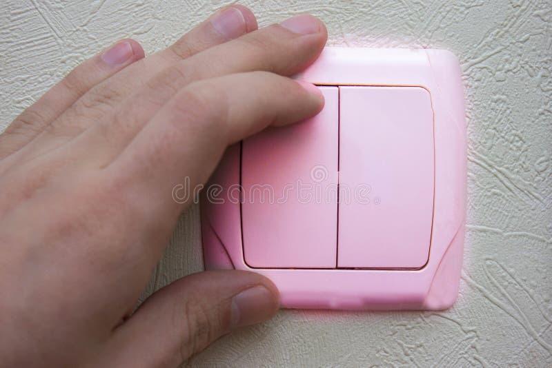 mano que mueve de un tirón el interruptor de la luz con la pared rosada foto de archivo