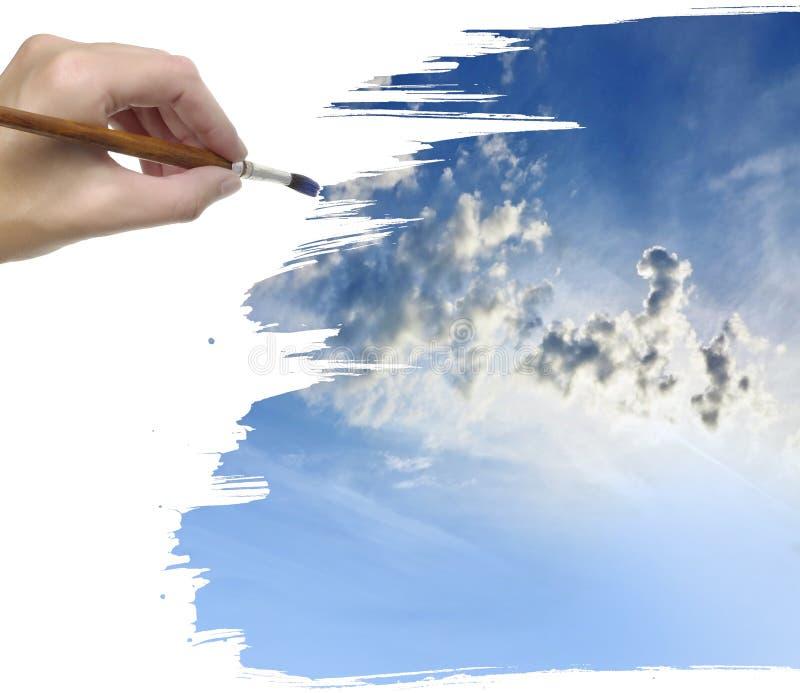Mano que pinta el cielo azul imagenes de archivo