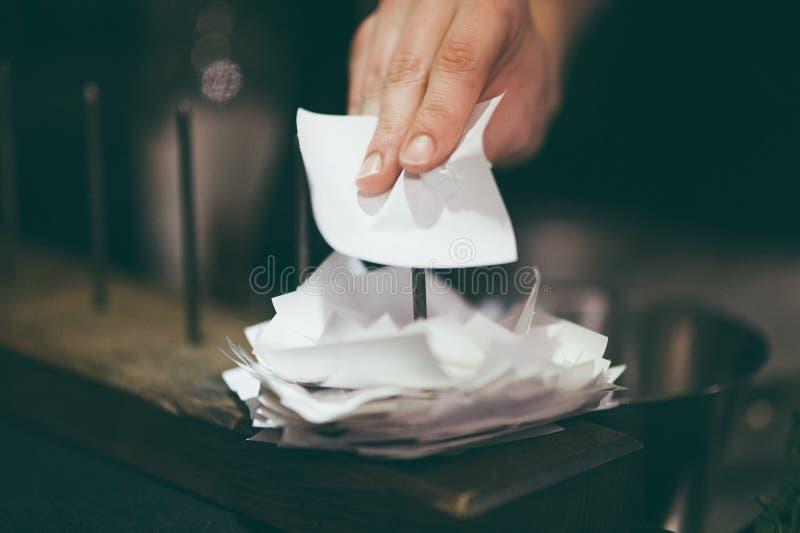 Mano que pone el boleto de la orden del restaurante en el palillo foto de archivo libre de regalías