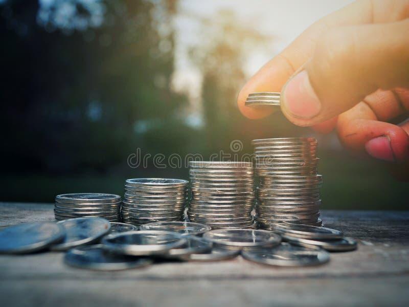 Mano que pone la moneda del dinero para apilar de monedas fotos de archivo libres de regalías