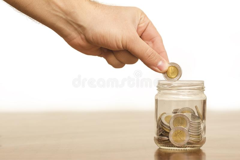 Mano que pone la moneda en un tarro por completo de las monedas, libras egipcias, Savin fotos de archivo