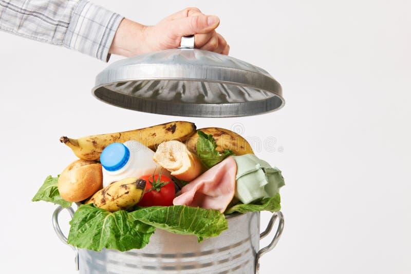 Mano que pone la tapa en el cubo de la basura por completo de comida inútil foto de archivo