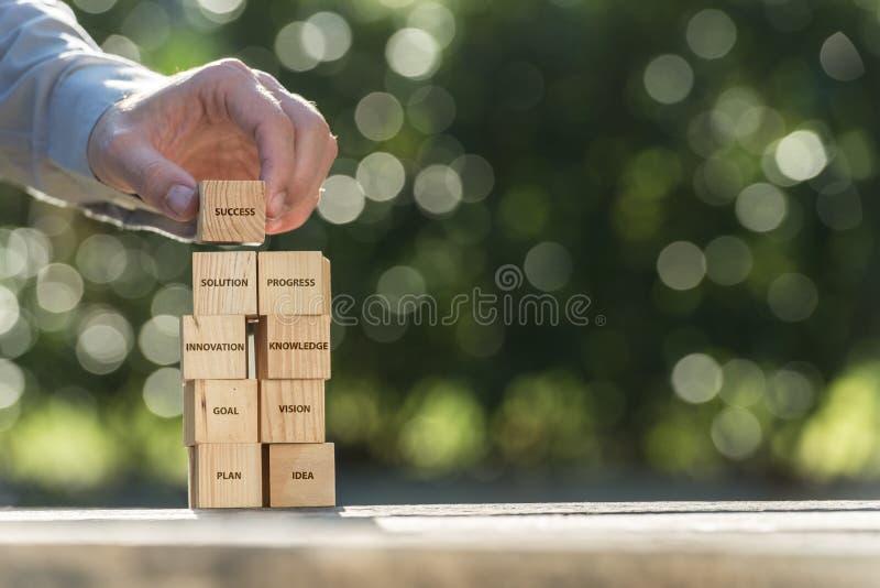 Mano que pone las unidades de creación de madera al éxito imagen de archivo