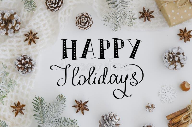 Mano que pone letras a la tarjeta de felicitación buenas fiestas en el fondo blanco Papá Noel en un trineo Decoración de la Navid fotografía de archivo libre de regalías
