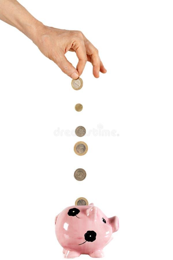 Mano que pone una moneda en moneybox foto de archivo libre de regalías