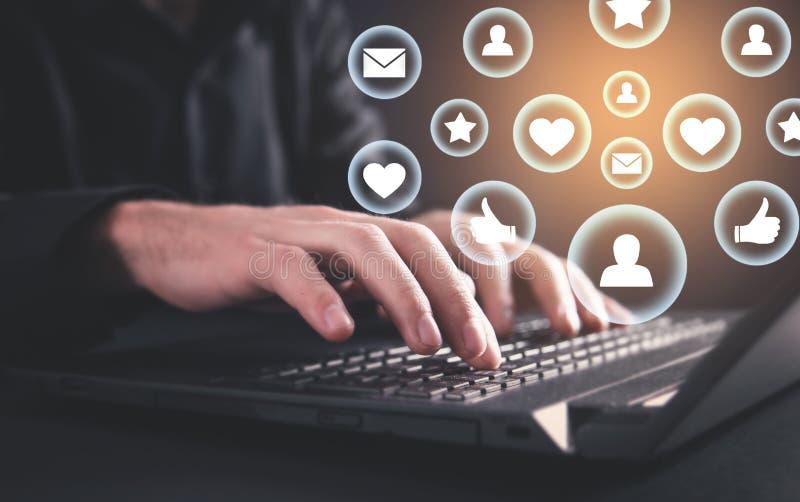 Mano que pulsa en el teclado de la computadora port?til Concepto social de los media imagen de archivo