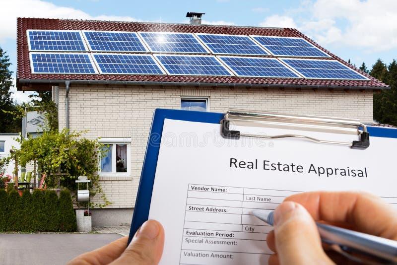 Mano que rellena el impreso de la valoración de Real Estate en Front Of House imagen de archivo libre de regalías