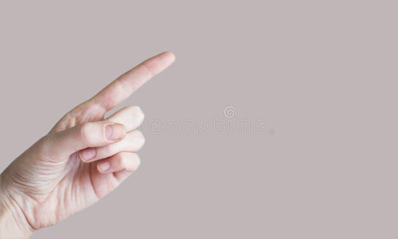 Mano que señala con el dedo índice en algo, espacio de la copia, fondo gris imagen de archivo