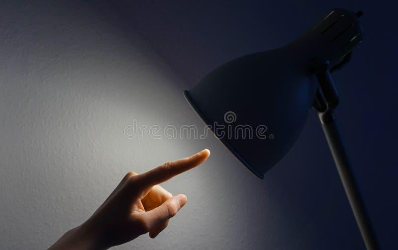 Mano que señala en una lámpara foto de archivo
