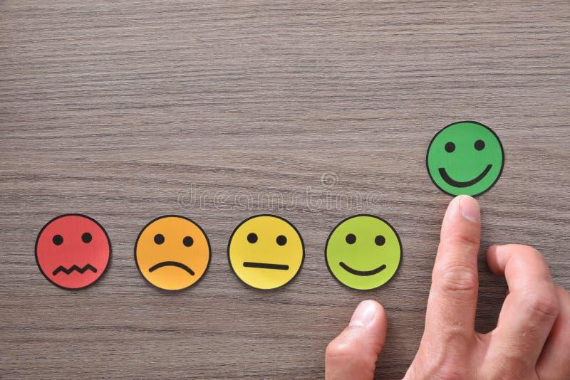 Mano que señala una satisfacción positiva representada con los emoticons en la tabla fotos de archivo