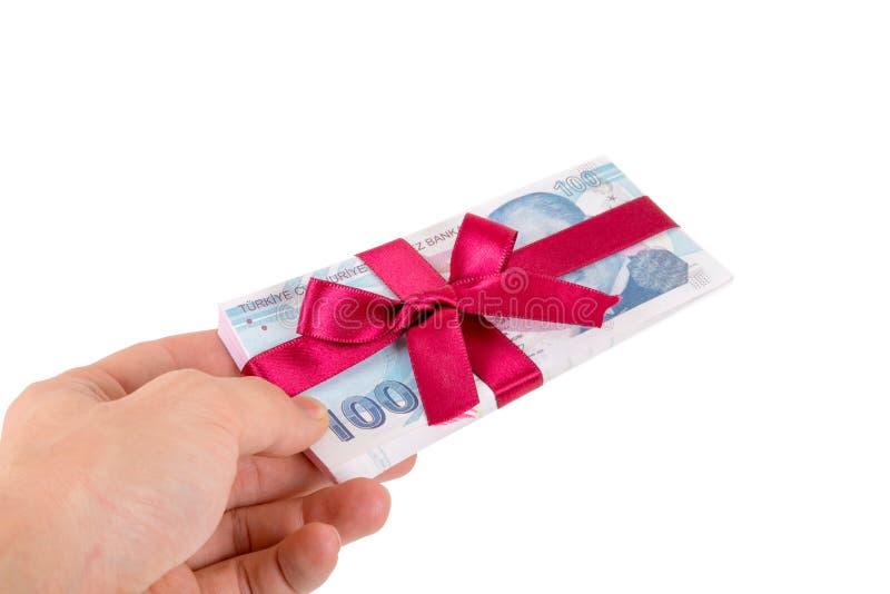Mano que sostiene billetes de banco de la lira turca con la cinta como regalo imágenes de archivo libres de regalías