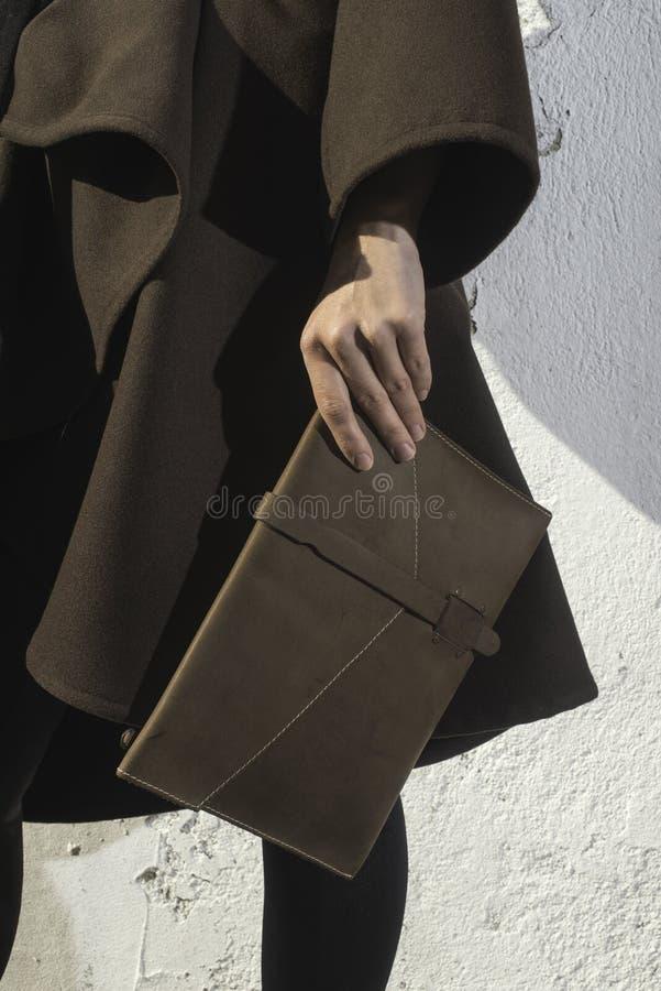 Mano que sostiene el bolso de cuero imagenes de archivo